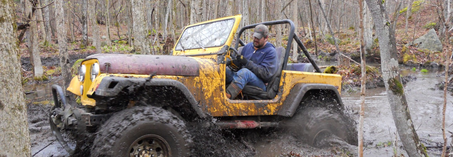 Joe Chase in Yellow Jeep CJ 7 with boggers in mud